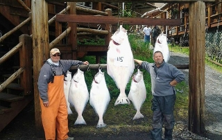 A couple of proud anglers stand next to their bounty during the Alaska fishing season.